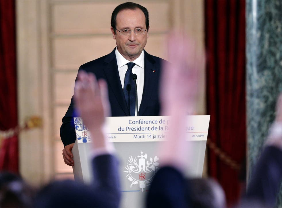 Reporters raise their hands during French President Francois Hollande's annual news conference