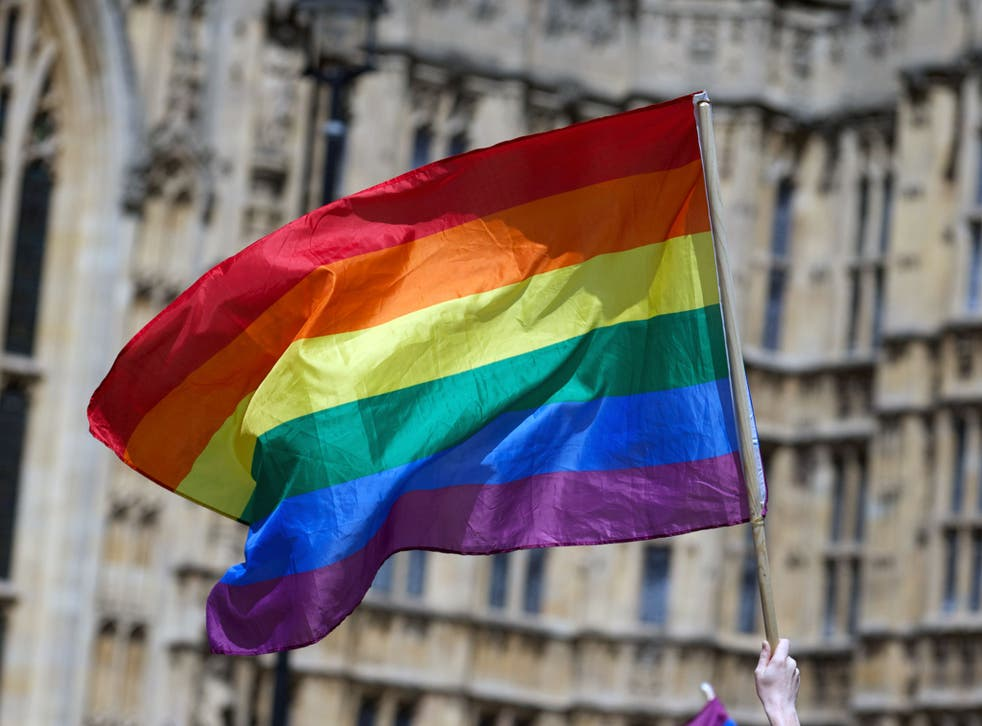 A gay campaigner waves the rainbow flag during a rally outside the Houses of Parliament as the Marriage (Same Sex Couples) Bill gets an unopposed third reading by the Lords in central London on July 15, 2013. Gay marriage was set to be legalised in Englan