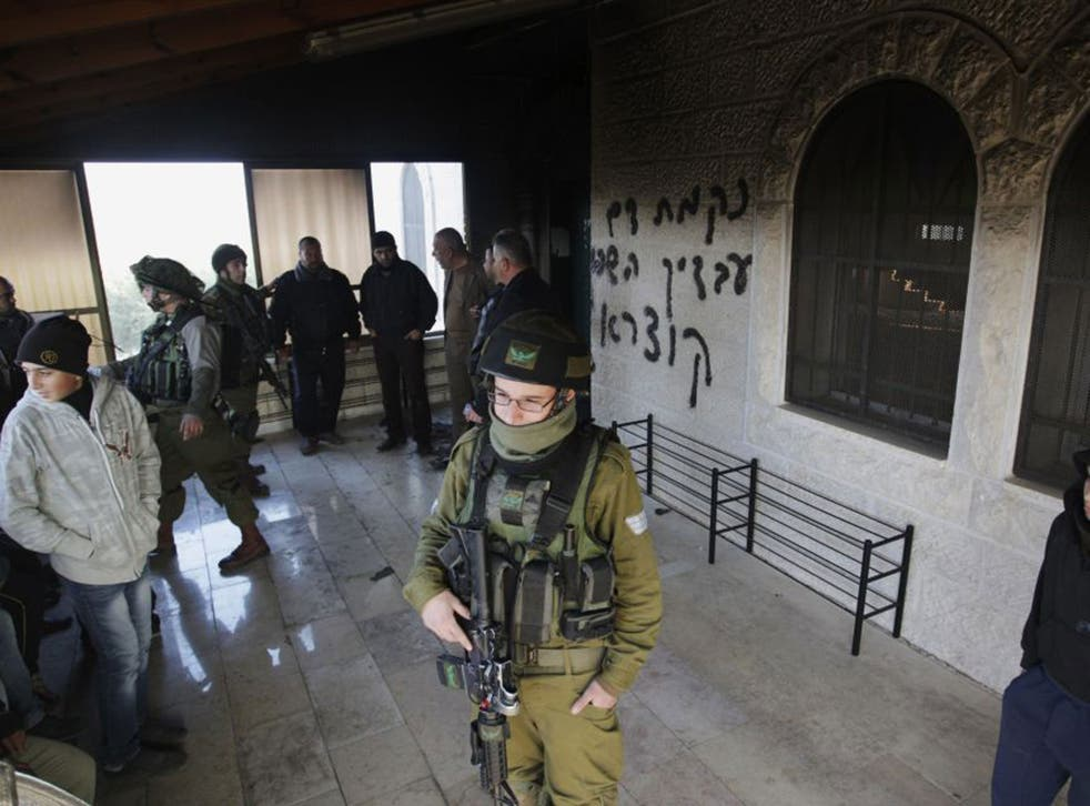 Israeli soldiers on guard at a West Bank mosque damaged by settlers