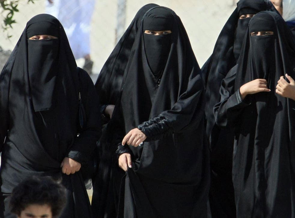 Saudi women cross a street in Hofuf city
