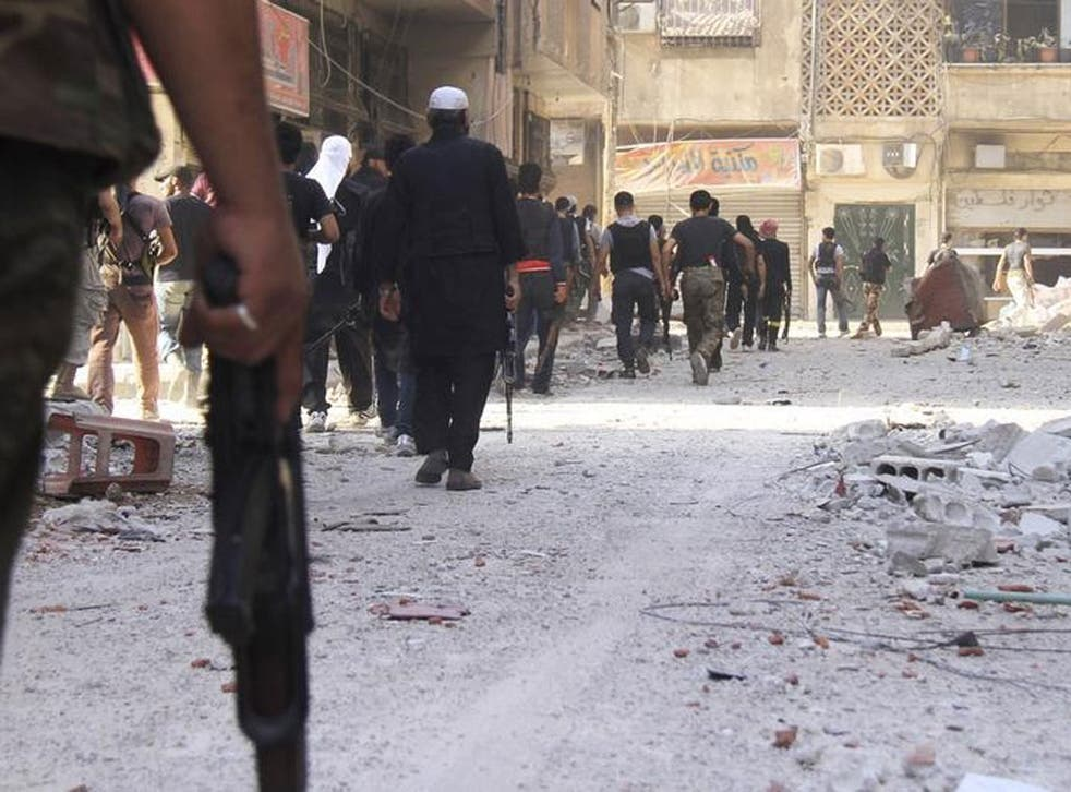 Free Syrian Army fighters carry their weapons as they walk towards the frontline in the refugee camp of Yarmouk, near Damascus