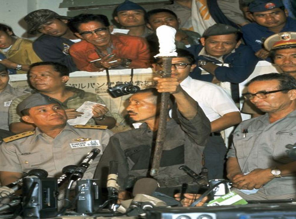 Former Japanese Imerial Army intelligent officer Hiroo Onoda (C) shows his Japanese sword during a press conference on March 10, 1974 in Lubang, Philippines. Leutinant Onoda, who spent almost 30-years holding out in the jungle on the Philippine island of