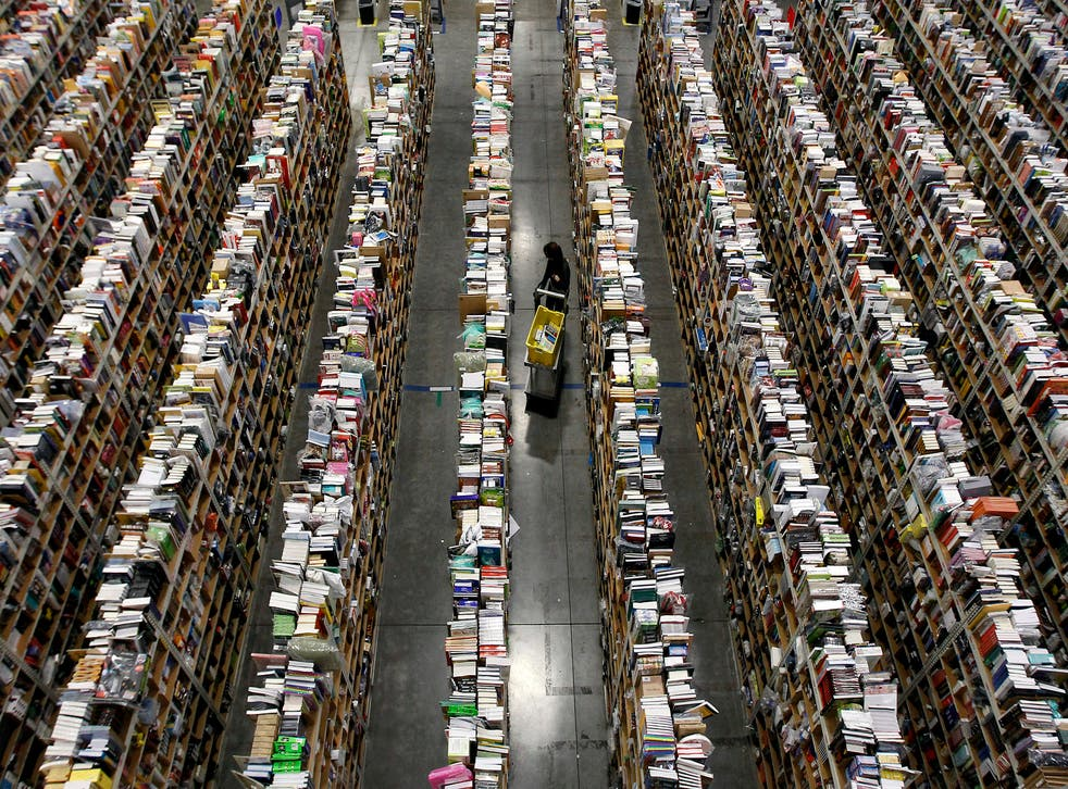 A worker gathers items for delivery from the warehouse floor at Amazon's distribution center in Phoenix, Arizona.