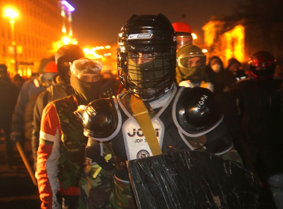 Protesters clad in improvised protective gear prepare for a clash with police in central Kiev