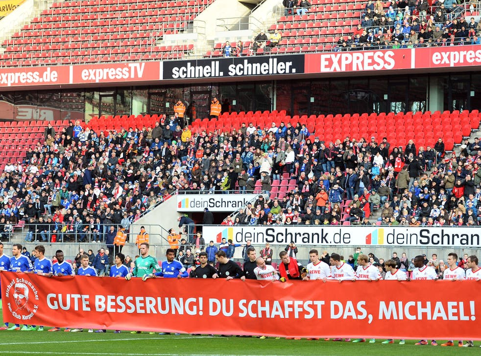 Players from Cologne (R) and Schalke (L) hold up a banner in tribute to Michael Schumacher, who is recovering from serious head injuries after a skiing accident