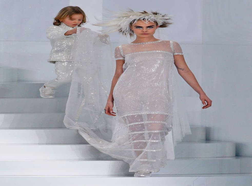 Cara Delevingne presents a creation from the Spring/Summer 2014 Haute Couture collection by German designer Karl Lagerfeld for Chanel fashion house during the Paris Fashion Week