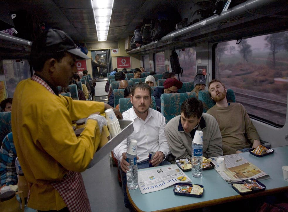 A waiter serves breakfast to passengers onboard the early morning Shatabdi Express train from New Delhi to Agra