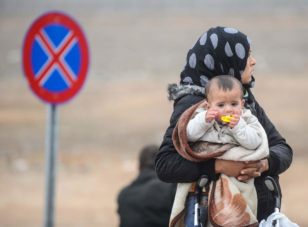 A Syrian woman with her baby at Syria's border with Turkey