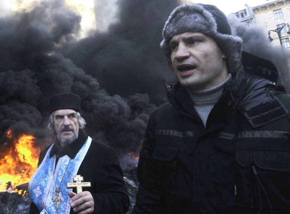 Opposition leader and former WBC heavyweight boxing champion Vitali Klitschko addresses protesters near the burning barricades between police and protesters in central Kiev