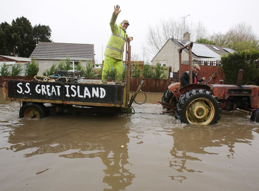A vintage tractor drives through flooded Thorney