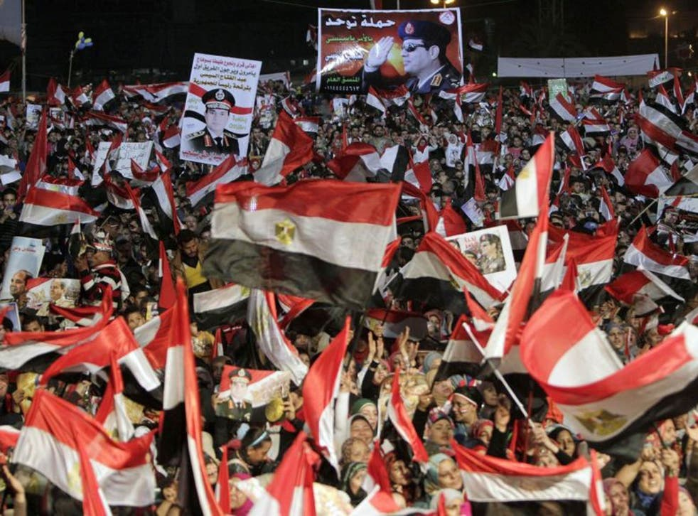 Supporters of Egypt's army chief General Abdel Fattah al-Sisi hold his posters in Tahrir square in Cairo, on the third anniversary of Egypt's uprising