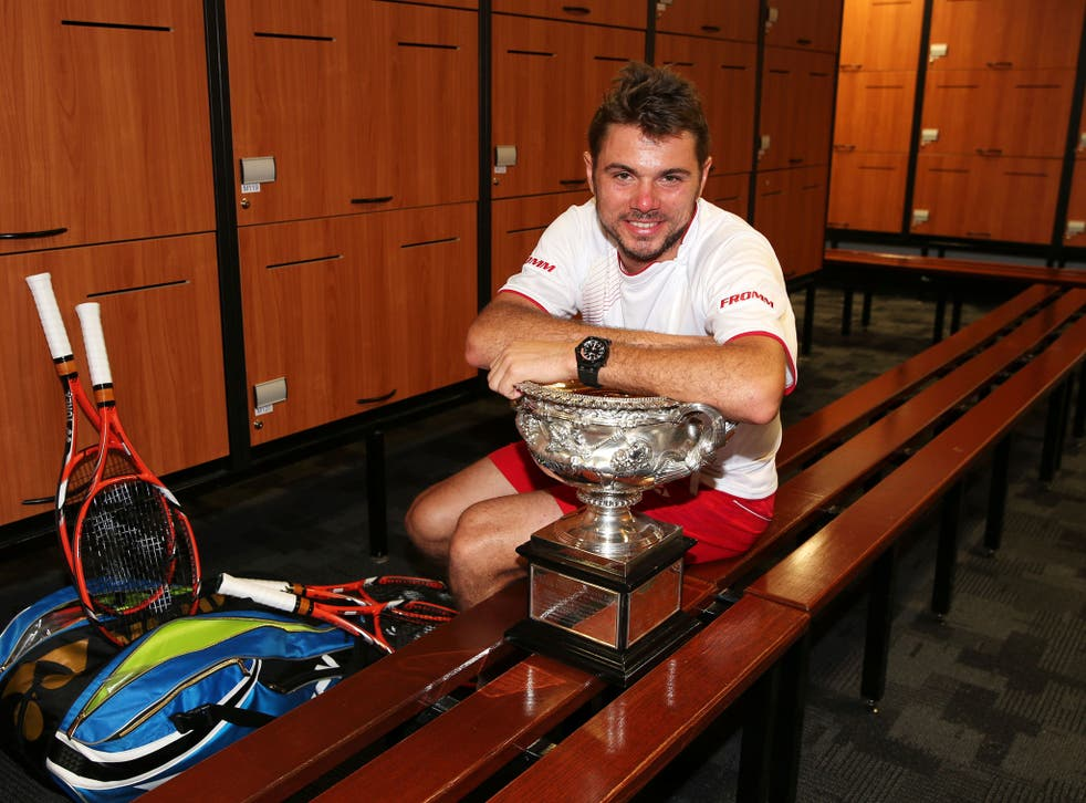 Switzerland's Stanislas Wawrinka poses with the Norman Brookes Challenge Cup in the players dressing room after winning his men's final match against Rafael Nadal