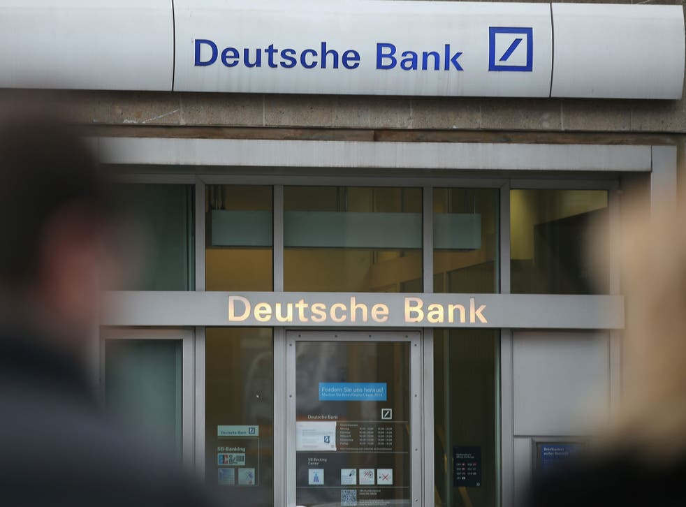 People walk past a branch of Deutsche Bank in Berlin, Germany