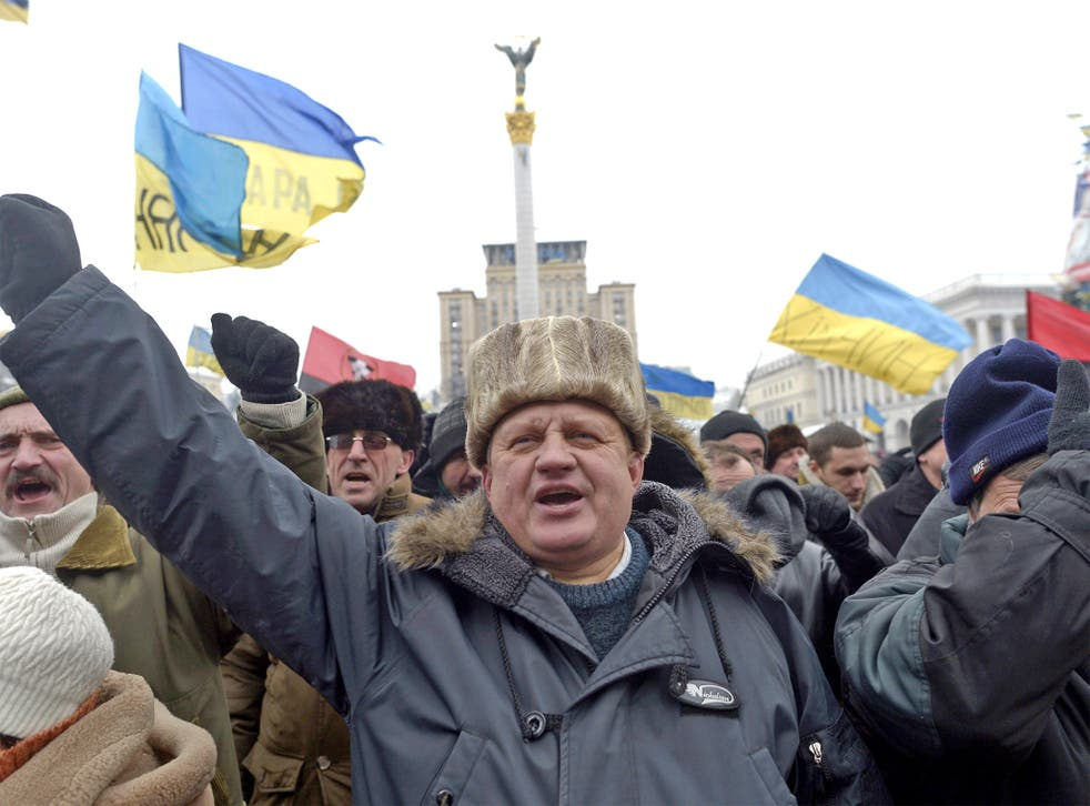 An anti-government protester raises his fist during a protest on Independence Square in Kiev