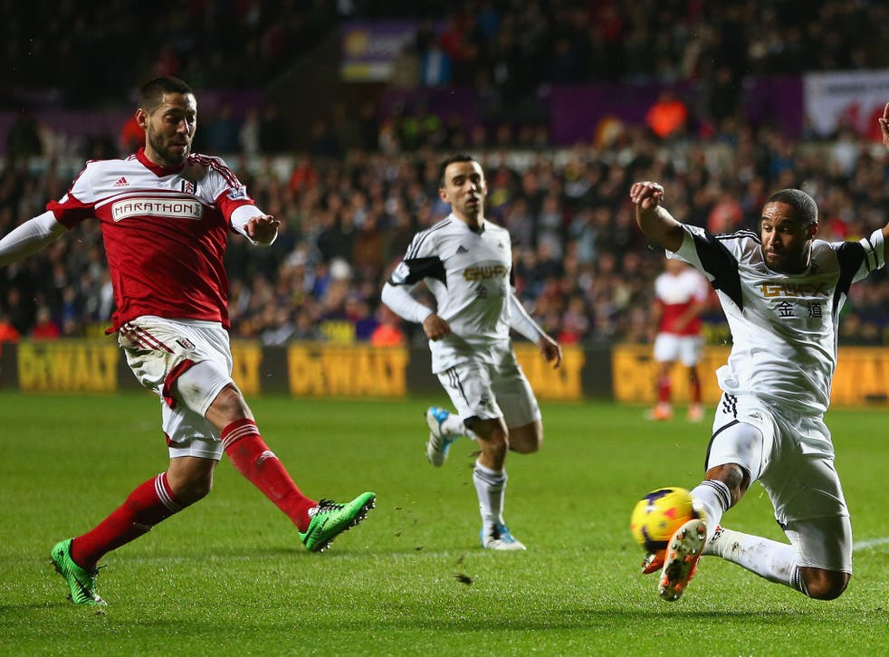 Clint Dempsey (L) of Fulham shoots as Ashley Williams (R) of Swansea City attempts to block