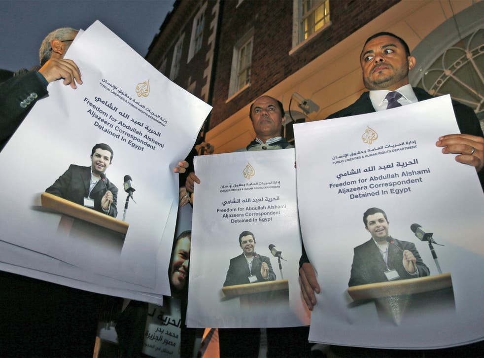 Demonstrators hold placards with pictures of Al-Jazeera journalist Abdullah Al Shami who - along with cameraman Mohammed Badr - remains in custody in Egypt, during a protest outside Egypt's embassy in London last November