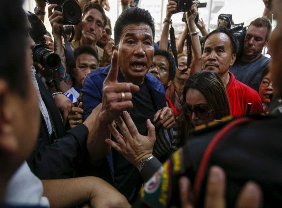Protesters demanding the right to vote argue with security and election officials at a district office where voting was called off in Bangkok