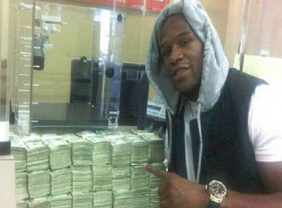 Floyd Mayweather, pictured in 2012 next to a large sum of money that triggered claims he has placed a $10.4m bet on the 2014 Super Bowl