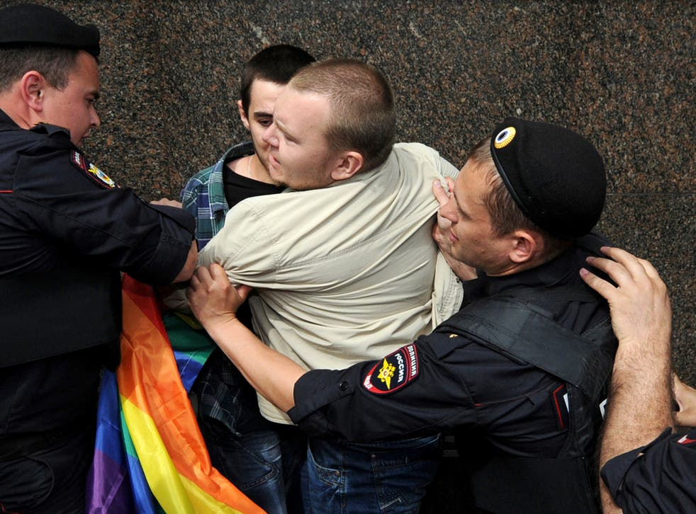 Russian riot policemen detain a gay and LGBT rights activist during an unauthorized gay rights activists rally in central Moscow on May 25, 2013.