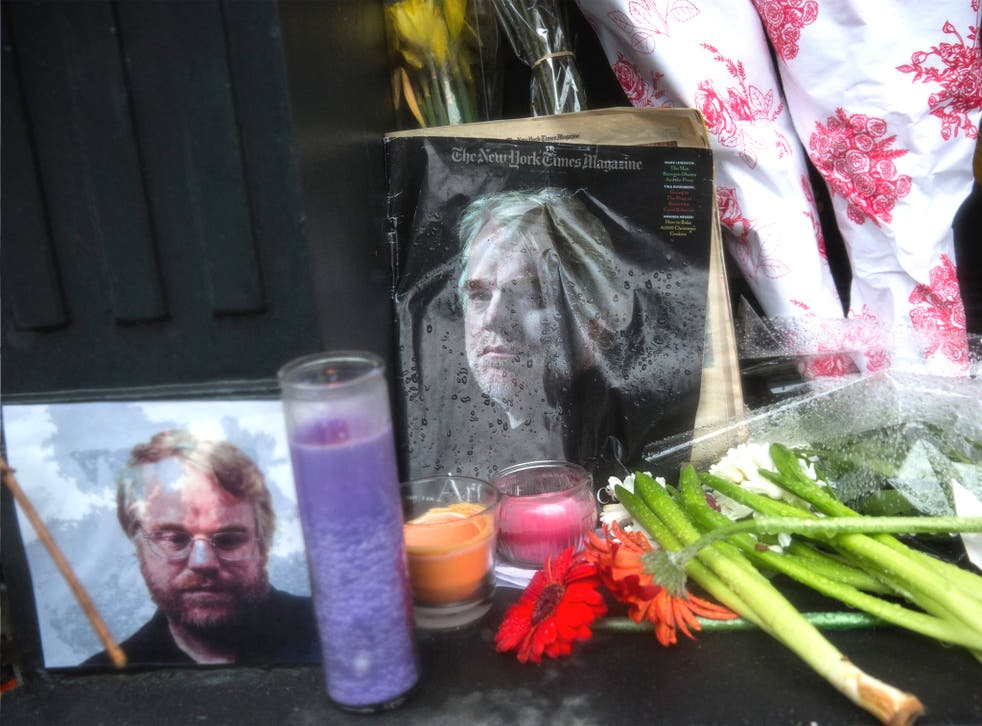 Candles, flowers and portraits sit outside the New York apartment of Phillip Seymour Hoffman