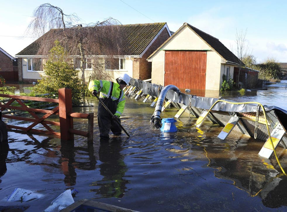 A member of the emergency services installing flood defences  in the village of Moorland on the Somerset Level