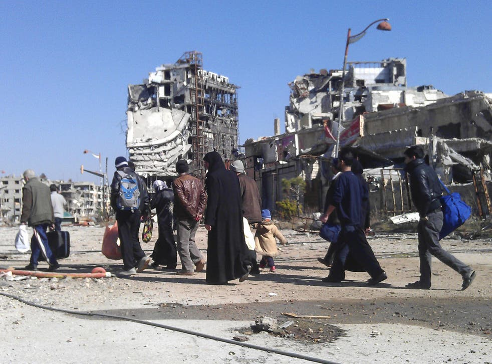 Civilians carry their belongings as they walk towards a meeting point to be evacuated from a besieged area of Homs