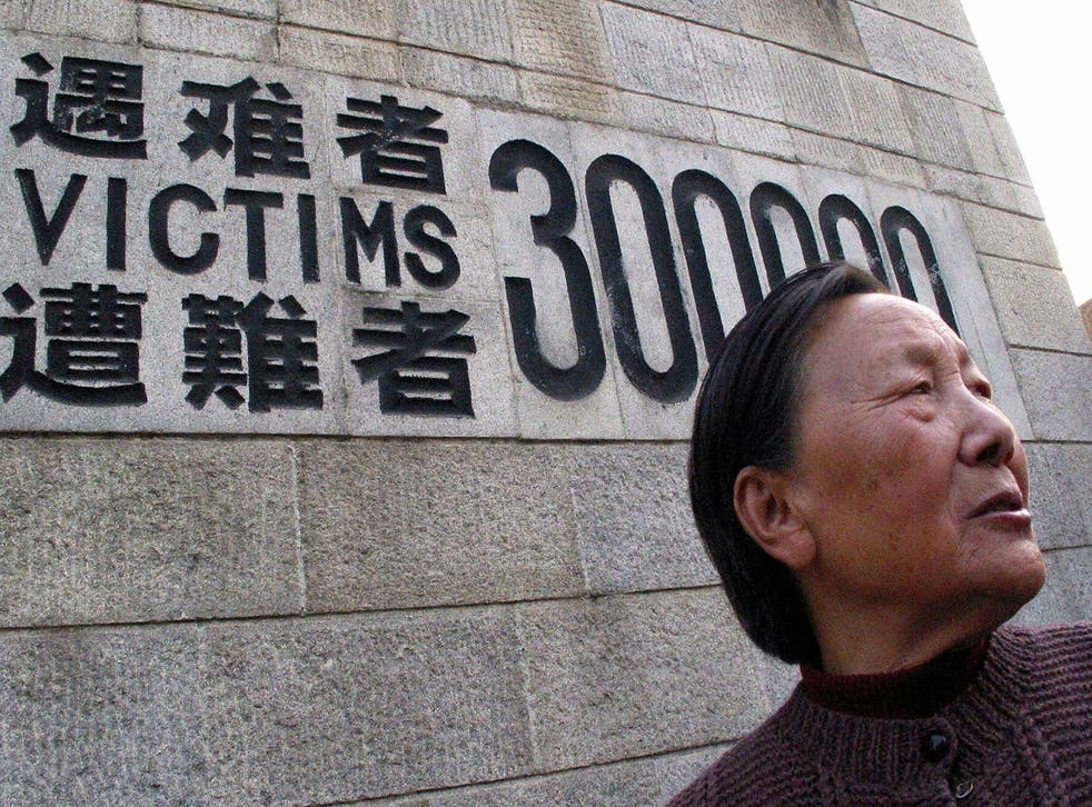 A man stands in front of the Monument for the Victims of the Nanjing Massacre.