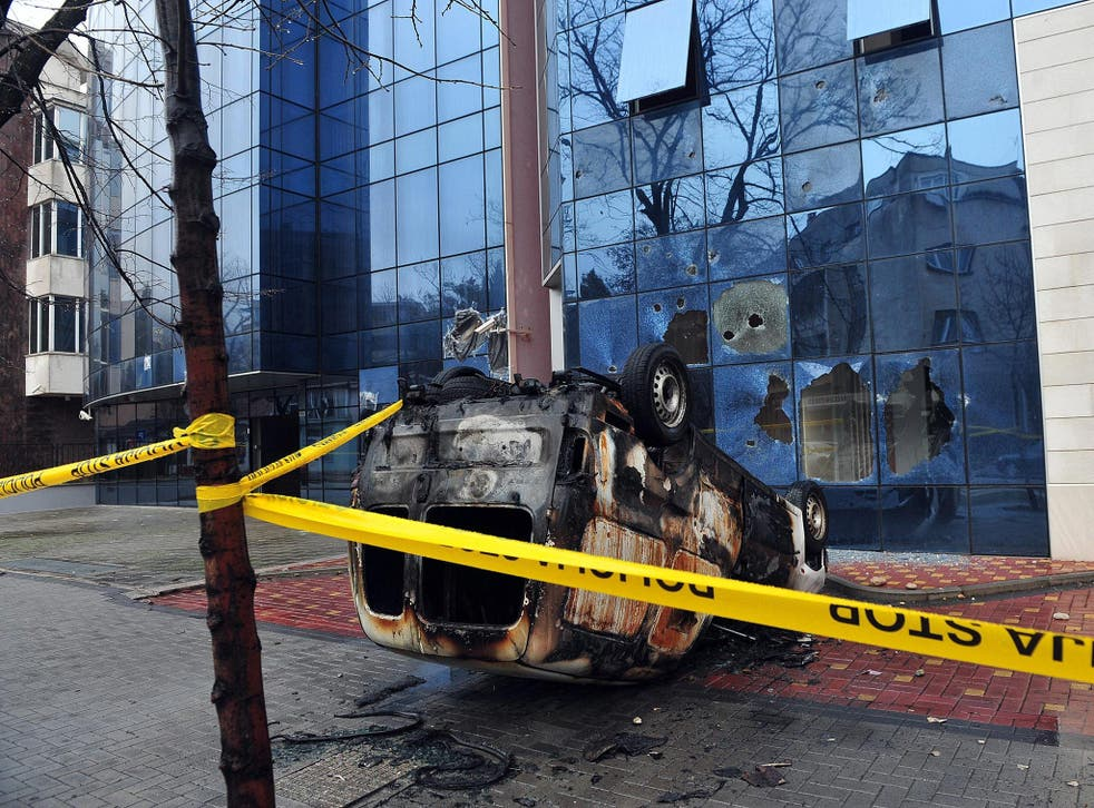 A burnt vehicle and windows broken by stones at the headquarters of the Croatian Democratic Union (HDZ) political party, in the Southern-Bosnian town of Mostar