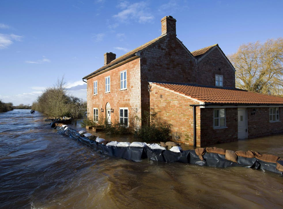 Flood waters engulf a house with a wall of sandbags around it in Burrowbridge