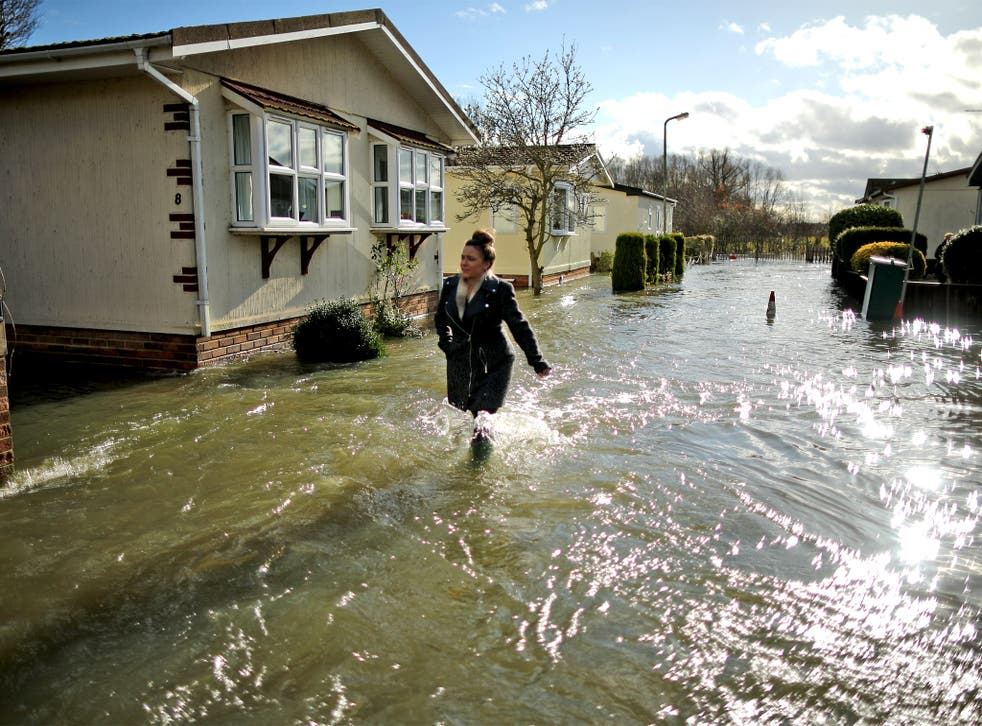 A resident wades through the floodwater that has swept into Chertsey, which lies just west of London