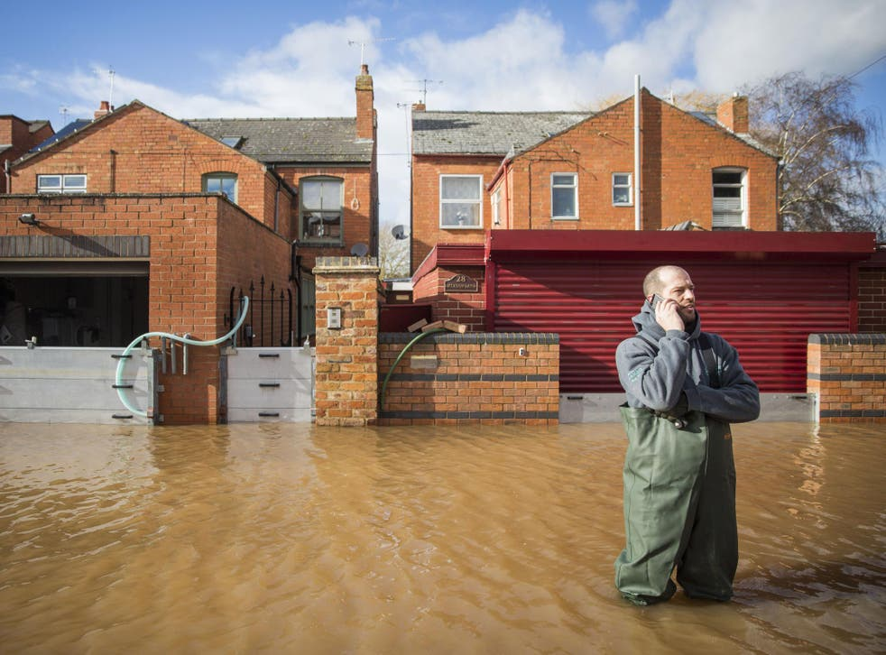 A resident of Waterworks Road stands in floodwater in Worcester