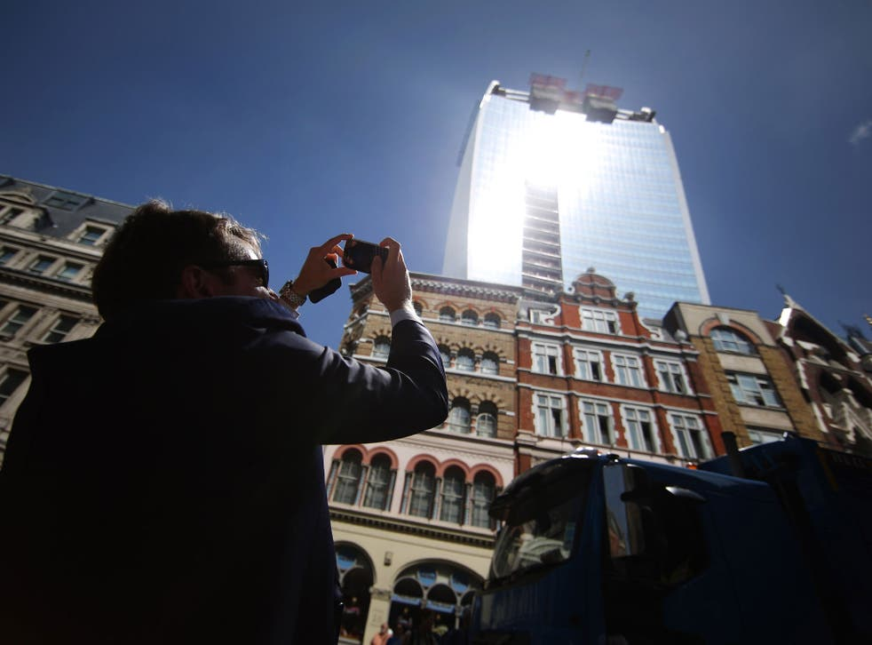 A man takes a photograph as the sun glares down from the Walkie Talkie building.