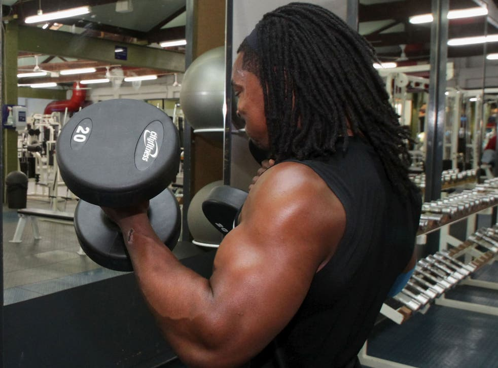 A man lifts weights in New Zealand. Researchers have found that people less inclined to exercise may be affected by a mutated gene