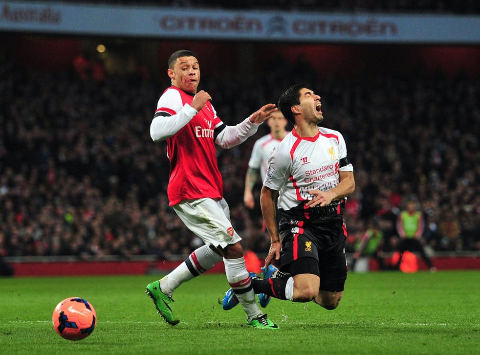 Liverpool's Luis Suarez is brought down by Alex Oxlade-Chamblerlain but referee Howard Webb refused to award a penalty