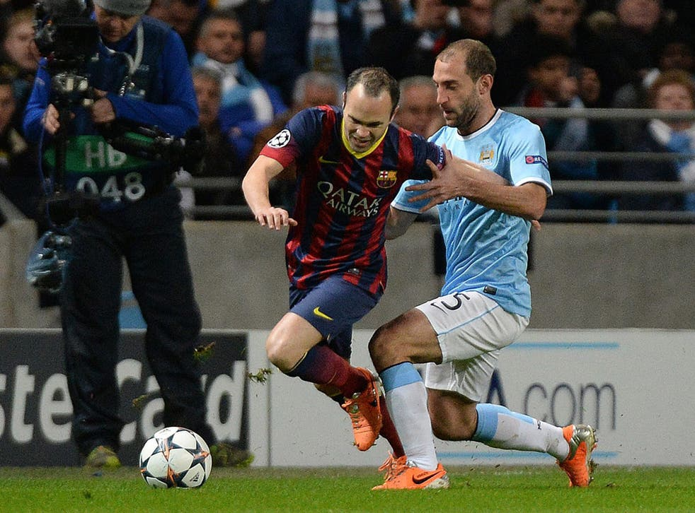 Andres Iniesta (left) is tackled by Manchester City's Pablo Zabaleta