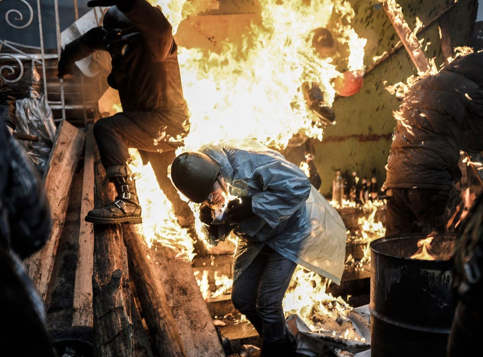 Protesters burn as they stand behind burning barricades during clashes with police on February 20, 2014 in Kiev.
