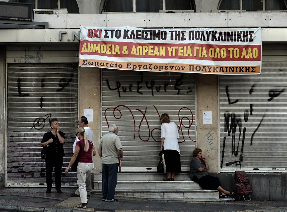 """People stand outside the """"Polyklikini"""", one of the hospitals affected by overhaul of the health sector"""