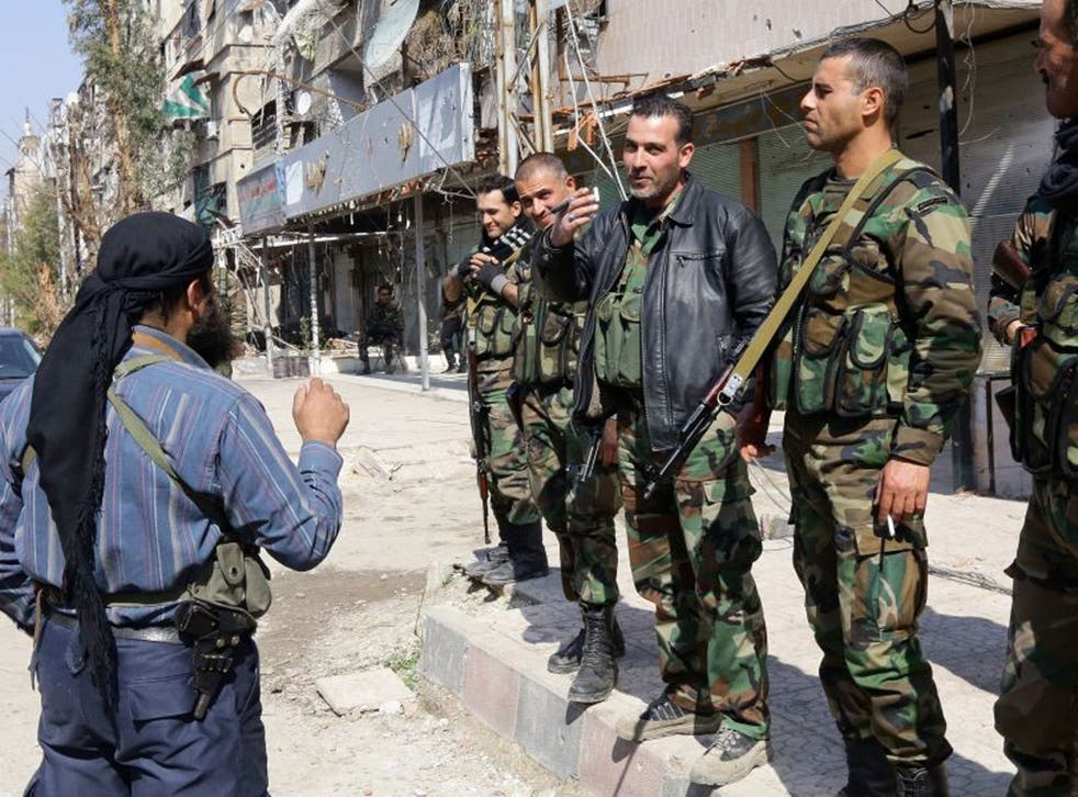 Time to talk: Pro-regime fighters speak to a rebel during a truce in Babbila, a Damascus suburb, earlier this month