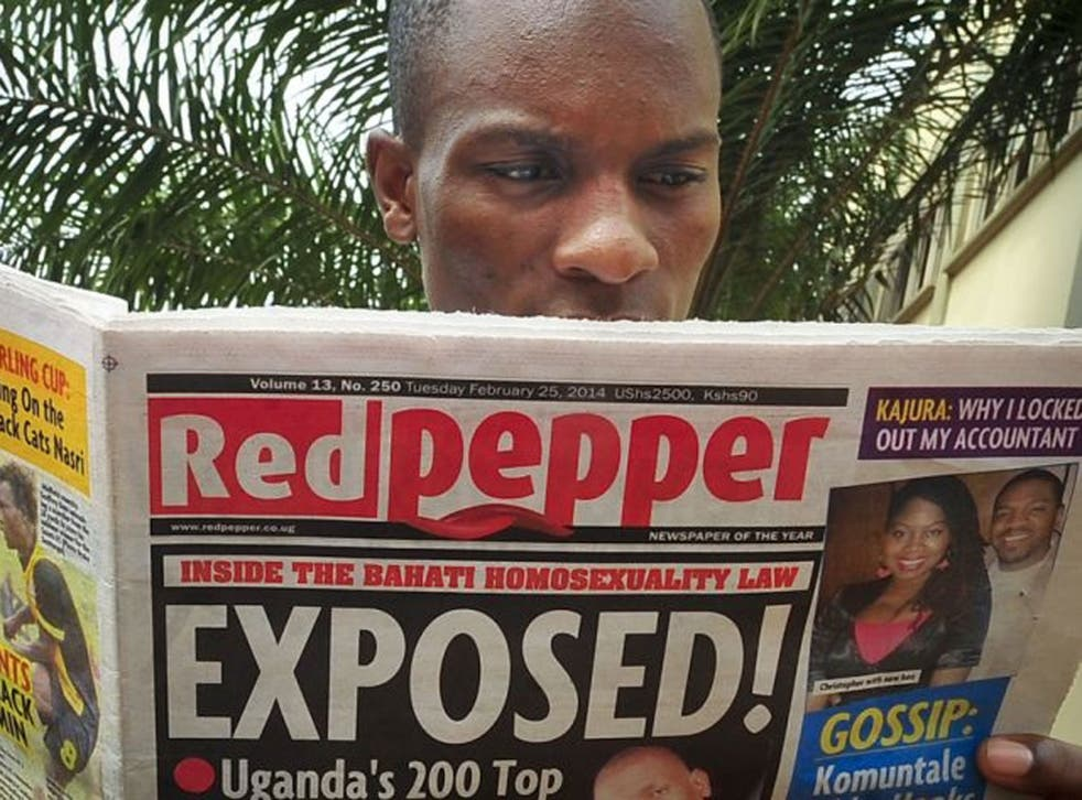 """A Ugandan reads a copy of the """"Red Pepper"""" tabloid newspaper."""