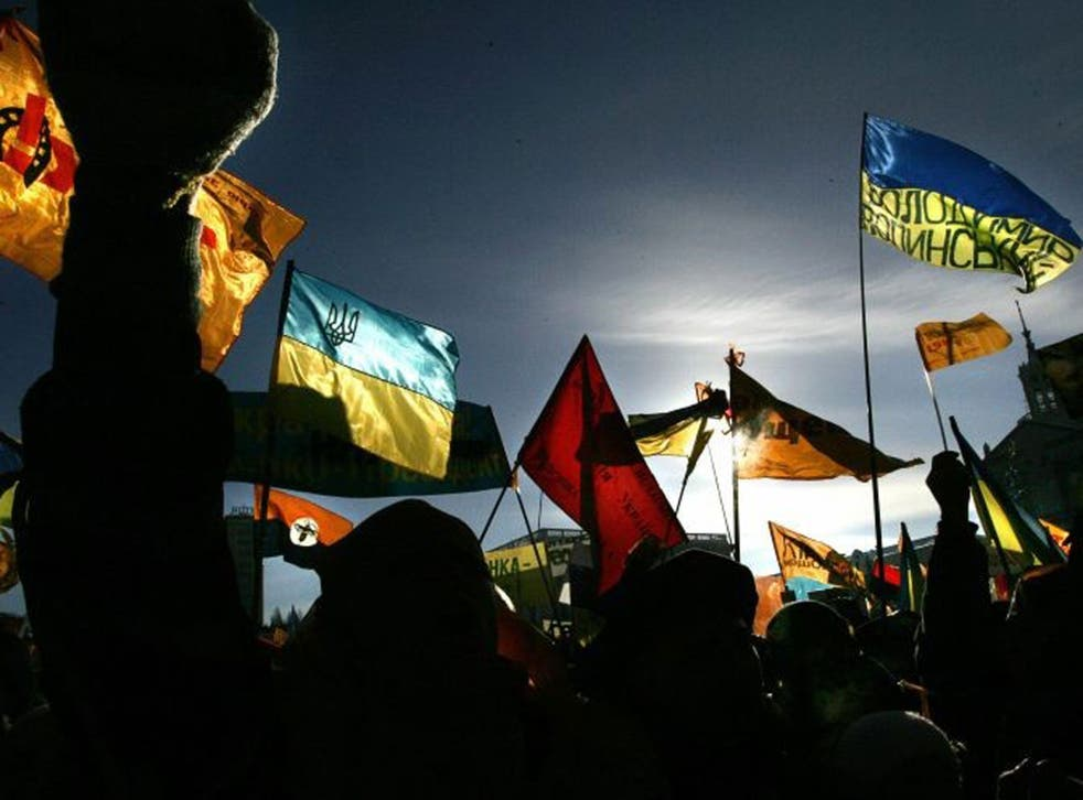 Silhouetted supporters of the pro-Western opposition leader Viktor Yushchenko wave flags during a rally in central Kiev