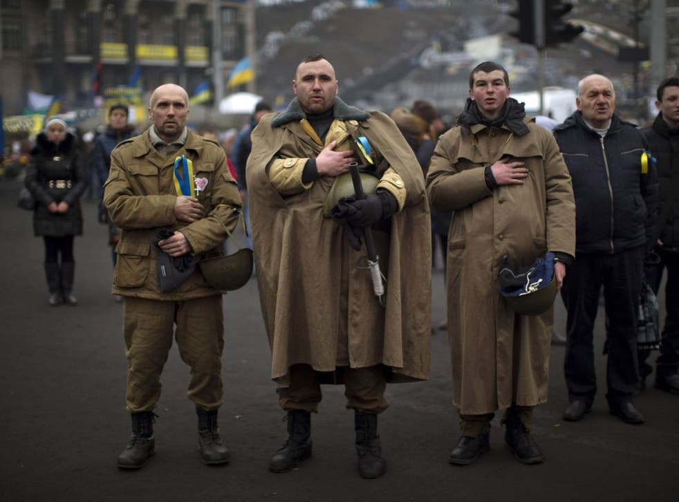 Ukrainians sing their national anthem in Kiev's Independence Square yesterday