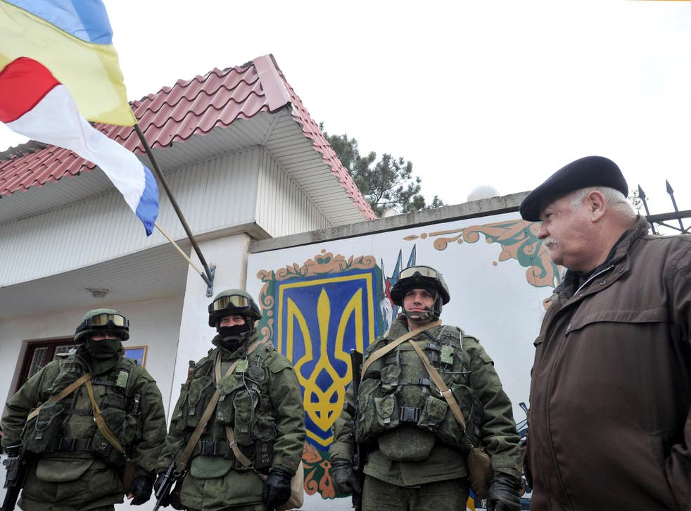 An Autonomous Republic of Crimea and a Ukrainian flag float side by side as a man watches armed men in military fatigues blocking access to a Ukrainian border guards base not far from the village of Perevalne near Simferopol