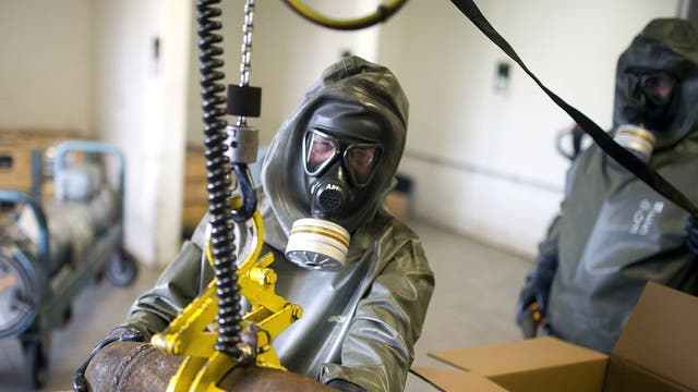 Workers in protective clothing holds a dummy grenade