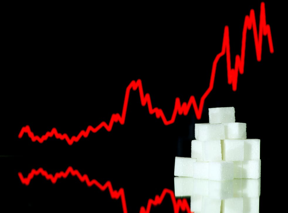 A picture taken on January 10, 2013 in Paris shows an illustration made with pieces of white sugar and a screen displaying the sugar exchange rate curve from 2002 to 2012.