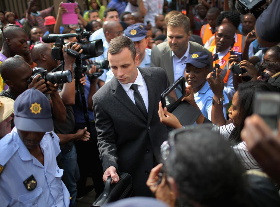 Oscar Pistorius is surrounded by police and media as he leaves North Gauteng High Court