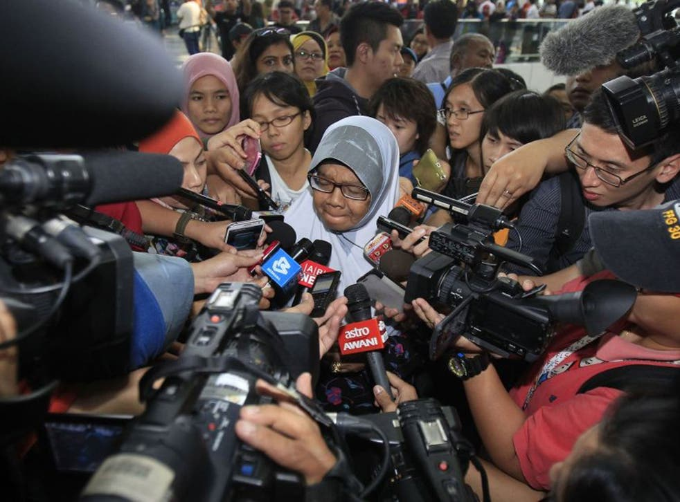 A family member of passengers aboard a missing Malaysia Airlines plane is mobbed by journalists at Kuala Lumpur International Airport