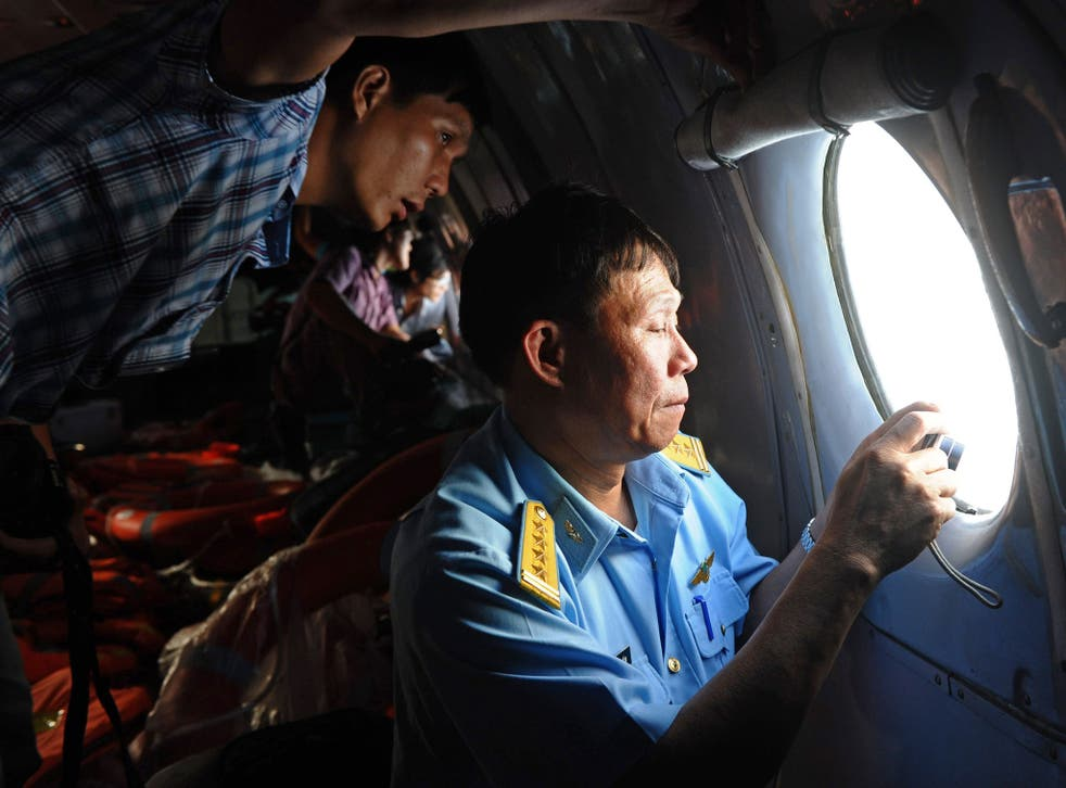 This picture taken from aboard a flying Soviet-made AN-26 used as a search aircraft by Vietnamese Air Force to look for missing Malaysia Airlines flight MH370, shows an officer, right, and a reporter, left, looking out the window during search operations