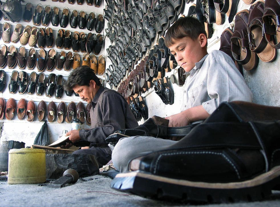 A Pakistani boy helps his father to make 'Chappal' or sandal at their workshop in Quetta - Paul Smith sell a £300 version in their London store