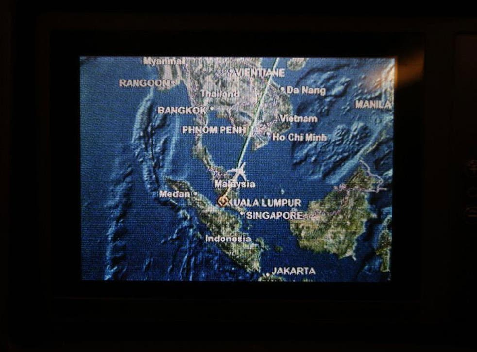 A screen on board Malaysia Airlines Boeing 777-200ER flight MH318 shows the plane's flight path as it cruises over the South China Sea from Kuala Lumpur towards Beijing at approximately the same point when flight MH370 lost contact with air traffic contro