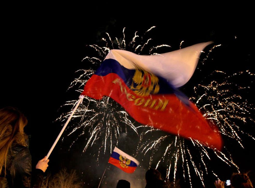 People wave Russian flags as fireworks explode in the sky over Sevastopol following the announcement of the result of the referendum